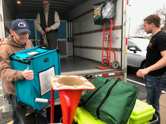 Fairfield County Board of Elections workers Jessee Aurant (left) and Trevor Harrison-Rawn unload voting equipment at the Liberty Center Tuesday after the state suspended the Ohio primary election due to the coronavirus pandemic.