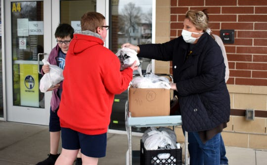 Food Services Worker Jennifer Wilson gives free meals to students at Mount Pleasant Elementary in Lancaster on Tuesday, March 17, 2020.