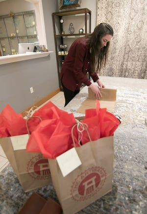 The Artisan's Bench Store Manager Brittany Campbell packages up an item for shipping Tuesday, May 17, 2020 in the downtown Brighton store. In the foreground are two packages prepared for curbside pickup.