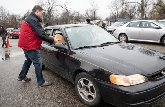 Todd Adams placed a box of frozen meals into a car at the Beechmont Community Center. March 17, 2020