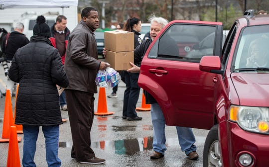 Bill Clark, right, takes boxes of food from Darrell Aniton, left, to place in a car at the at the Beechmont Community Center. March 17, 2020