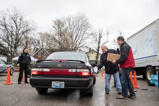 Bill Clark opens a car door for Todd Adams to land a box of frozen meals at the Beechmont Community Center. March 17, 2020