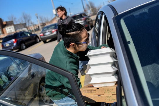 Volunteer Sam Klahn loads pizzas and salads into his car that he's delivering to people in need after picking up the food from The Fledge on Tuesday, March 17, 2020, in Lansing. High Caliber Karting donated 50 ready-to-bake pizzas and 50 salads along with some fruit and vegetables to The Fledge to be handed out or delivered to people in need. High Caliber Karting, located at the Meridian Mall, is temporarily closed due to COVID-19 and gave away the food before it went bad.