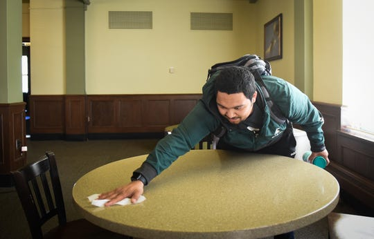 """I'm not gonna lie, I was a bit irresponsible last week but as things are getting more serious, I'm now doing my part and being very cautious,""  Michigan State University junior business major Joe Madrid of Yuma, Arizona as he wipes down a table before sitting down to study, Tuesday, March 17, 2020, in Philips Hall."