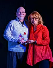 Northpointe Community Church pastor Rick Ruble accepts the award from Paula Cunningham of AARP.