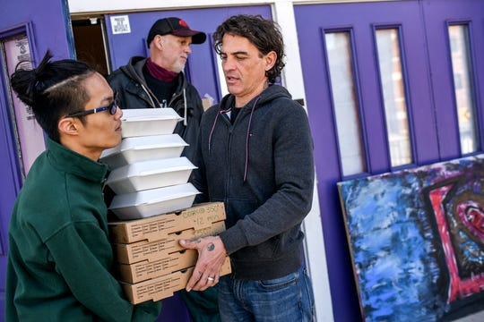 Jerry Norris, CEO of The Fledge, right, hands volunteer Sam Klahn pizzas and salads to be delivered to people in need on Tuesday, March 17, 2020, in Lansing. High Caliber Karting donated 50 ready-to-bake pizzas and 50 salads along with some fruit and vegetables to The Fledge to be handed out or delivered to people in need. High Caliber Karting, located at the Meridian Mall, is temporarily closed due to COVID-19 and gave away the food before it went bad.