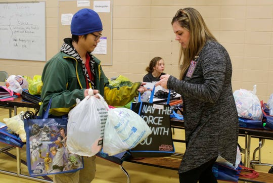 Kong Moua of Manitowoc, picks up bags of school homework from teacher Nicole Theel for his four children who attend Madison Elementary School during a homework pickup, Tuesday, March 17, 2020, in Manitowoc, Wis.  Manitowoc Public Schools will be conducting classes online during the COVID-19 crisis.