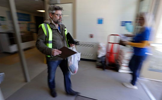 Manitowoc music teacher David Bourgeois is a blur of action as he carries out homework to awaiting parents, Tuesday, March 17, 2020, in Manitowoc, Wis. Manitowoc Public Schools will be conducting classes online during the COVID-19 crisis.