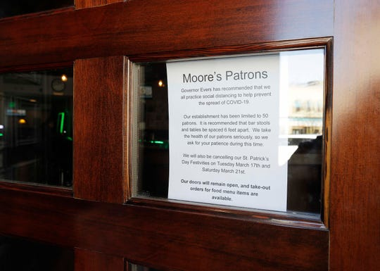 Moore's Irish Pub door had a sign indicating patron limits as seen, Tuesday, March 17, 2020, in Manitowoc, Wis. All bars and restaurants were ordered closed by the state. The firm also cancelled its St. Patrick's Day festivities.