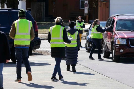 Franklin School staffers carry homework to waiting parents outside the school, Tuesday, March 17, 2020, in Manitowoc, Wis. Manitowoc Public Schools will be conducting classes online during the COVID-19 crisis.