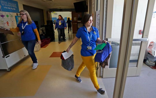 Franklin Elementary School staffers carry packages of educational items to waiting parents, Tuesday, March 17, 2020, in Manitowoc, Wis. Manitowoc Public Schools will be conducting classes online during the COVID-19 crisis.