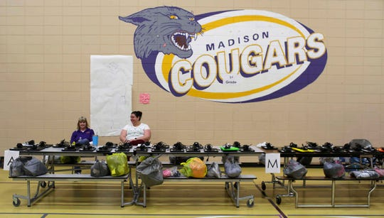 Madison Elementary's gym is filled with homework bags and chrome books and homework bags ready for pickup, Tuesday, March 17, 2020, in Manitowoc, Wis. Manitowoc Public Schools will be conducting classes online during the COVID-19 crisis.