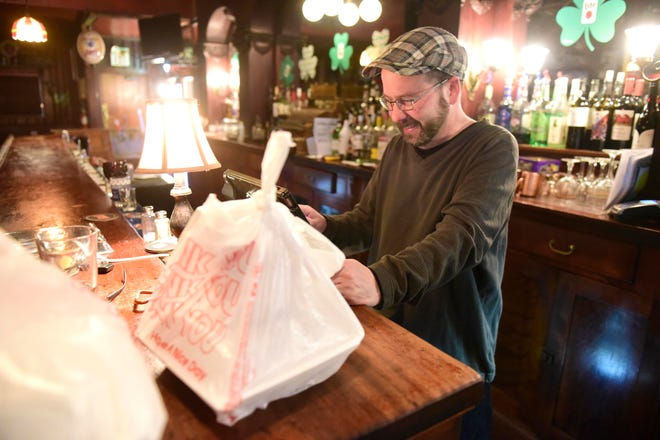 Lance Gutchall rings out a to-go order Monday night at Weber's Bar in Shelby.