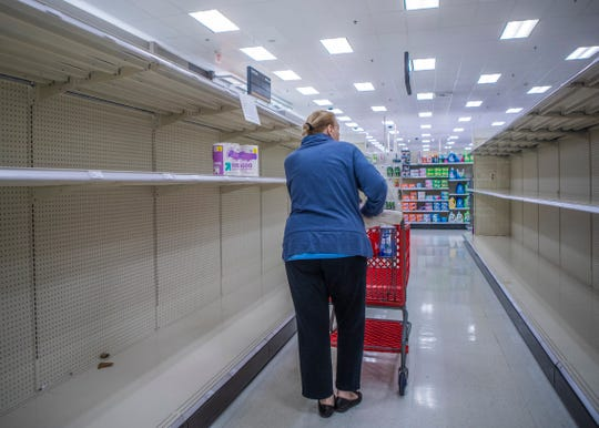 A Target customer walks down the paper product aisle as the toilet paper shelf is almost  empty at  Target in Germantown,Tenn., on Tuesday, March 17, 2020.