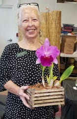Linda Walker shows her first place orchid.
