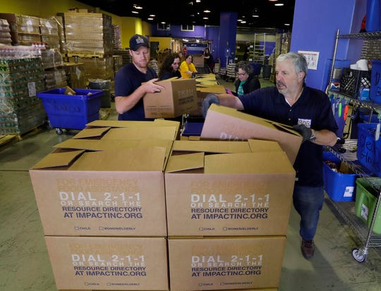 From left, Hunger Task Force  workers Chris Bylsma  and Bob Brazner load boxes for distribution to  more than 10,000 senior citizens in southeast Wisconsin, Tuesday, March 17,2020.  Nearly 90% of Hunger Task Force's current network of pantries is voluntary and help is crucial. Small groups of 15-20 are needed to help build Stockboxes.