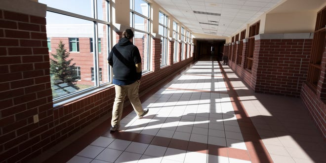 A student goes to collect school materials on the first day of mandatory statewide school closures Tuesday, March 17, 2020 at Fond du Lac High School in Fond du lac, Wis.