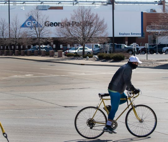 A bicyclist rides past Georgia Pacific's facility on S. Broadway on Tuesday, March 17, 2020 in Green Bay, Wis. According to the company, they have about 2,300 Georgia-Pacific (GP) employees working in Green Bay. About 1,725 mill employees manufacture and distribute leading commercial and retail brands of paper products (bath tissue, napkins, towels) and about 600 business support employees provide engineering, transportation, data processing, and customer services.