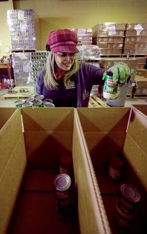 Hunger Task Force staff worker Michele McCormack fills a box with food items for senior citizens in southeast Wisconsin.