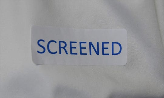 """Visitors to Baxter Regional Medical Center are screened for possible coronavirus exposure prior to being admitted into the building. Those clearing the screening process are given """"Screened"""" stickers to denote their status."""