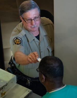 Security checks the temperature of people entering the Montgomery County Courthouse buildings in Montgomery, Ala., during the coronavirus outbreak on Tuesday March 17, 2020.