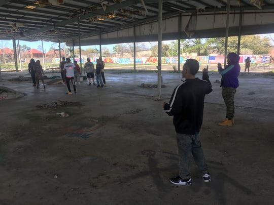 Noah Baker, second from right, speaks to the artists during filming for his Alabama Massacre 11 project  at an old warehouse site in Montgomery.
