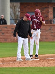Prattville coach Kevin Hall meets Will Smith on third base.