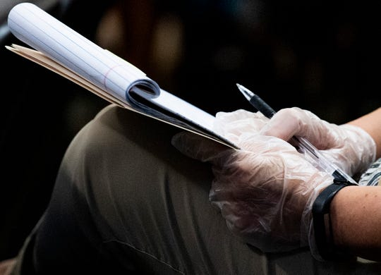 A county official wears gloves and takes notes during an emergency County Commission meeting in Montgomery, Ala., during the coronavirus outbreak on Tuesday March 17, 2020.