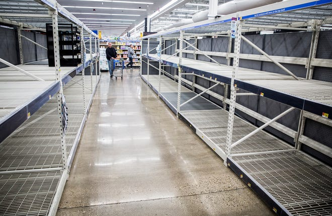 Customers at the northside Muncie Walmart peruse empty aisles Tuesday morning. Employees at the store were busy keeping shelves stocked as people prepared for possible quarantine.