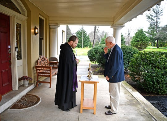 The Rev. Thomas McKenzie serves communion to Don Klein who came by for the drive-thru communion outside the Church of the Redeemer in Nashville, Tenn. Tuesday, March 17, 2020.