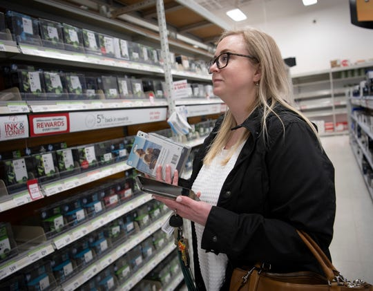 """Rachel Rail looks for items at an office supply store as she shops for a neighbor shut-in by the coronavirus outbreak Tuesday, March 17, 2020 in Nashville, Tenn. """"It makes me feel like I can do something instead of just sitting in my house not doing anything"""" said Rail about the pandemic."""