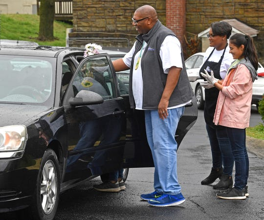 Bordeaux Center Director Melvin Fowler passes out flowers while others fill a car with groceries and a hot meal to FiftyForward Bordeaux members Tuesday.