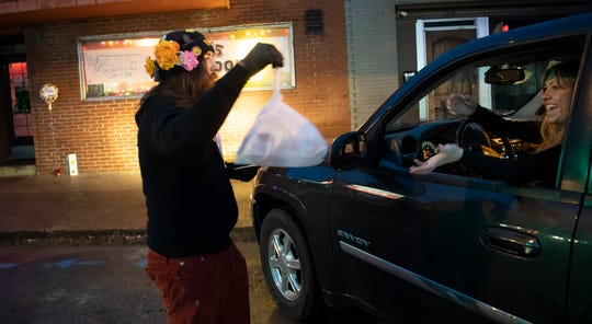 "Dino's kitchen manager Taylor ""Dip"" Varnell delivers a take-out order to Jennifer Perry outside the restaurant Monday, March 16, 2020 in Nashville, Tenn. Dino's Restaurant has moved to only take-out food after closing their dining room in the wake of the coronavirus outbreak."