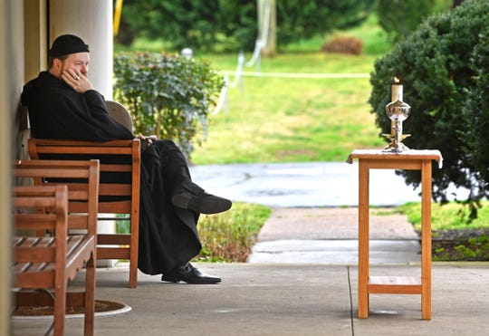 The Rev. Thomas McKenzie waits on the front porch of the Church of the Redeemer where he is hosting drive-thru communion this week and probably next in Nashville, Tenn. Tuesday, March 17, 2020.