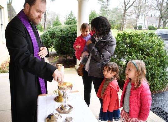 Carolyn Brasel has communion with her daughters Hope, Elly Rose and Aimee delivered by the Rev. Thomas McKenzie, who is hosting drive-thru communion outside his church this week and probably next at the Church of the Redeemer in Nashville, Tenn. Tuesday, March 17, 2020.