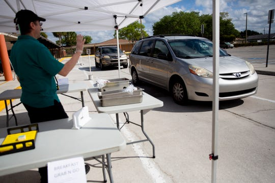 Nutrition Services employee Scott Richard directs drivers as they line up for bagged lunches and breakfasts at Golden Terrace Elementary School in Golden Gate on Tuesday, March 17, 2020.