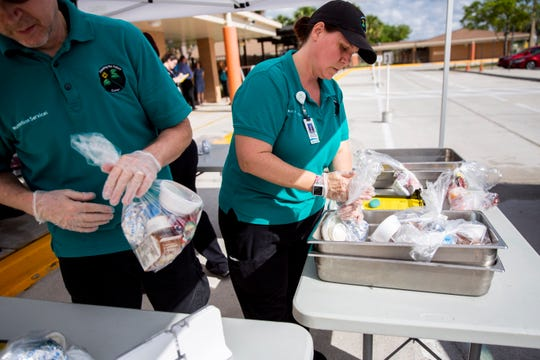 Nutrition Services employee Scott Richard, left, and guest manager Jamie Soto, right, prepare bagged lunches and breakfasts to hand out at Golden Terrace Elementary School in Golden Gate on Tuesday, March 17, 2020.