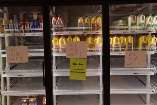 Signs asking customers to limit themselves to one container of milk at Ross' Granville Market. The store has placed limits on many items. As of Tuesday limited items included paper towels, toilet paper, water, toilet bowl cleaner, bleach, sanitizing wipes, sanitizer, Lysol, flour, sugar, eggs, and milk.