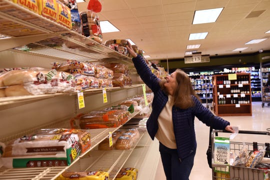 Sue Molnar grabs a loaf of bread while shopping at Ross' Granville Market. Signs were posted asking customers to limit themselves to one package of bread and one of buns. The store has placed limits on many items. As of Tuesday limited items included paper towels, toilet paper, water, toilet bowl cleaner, bleach, sanitizing wipes, sanitizer, Lysol, flour, sugar, eggs, and milk.