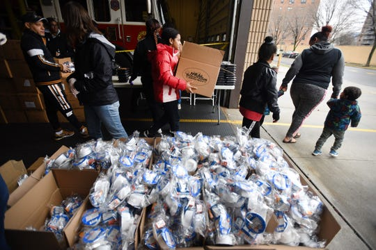 Residents exit after receiving boxes of food as Paterson district distributes what had been in-school breakfasts and lunches to local residents due to the school closures, at Northside Firehouse in Paterson, Tuesday on 03/17/20.