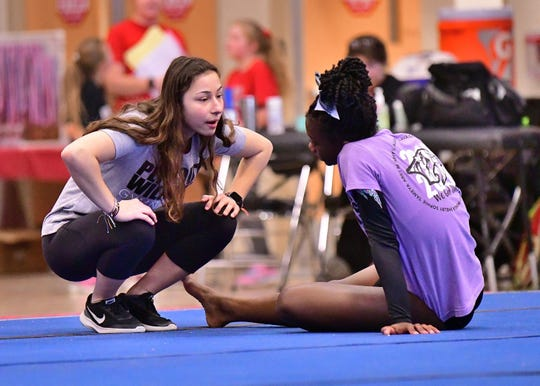 Plymouth gymnastics assistant coach Adrian Hartford joined the coaching staff one year after graduating from Plymouth High School.