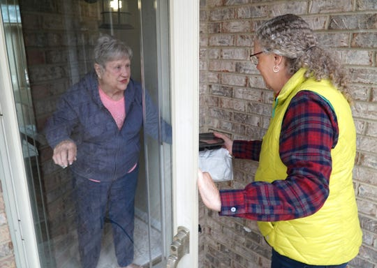 Milford resident Marie Jackson, left, welcomes a Meals on Wheels delivery from volunteer Jennifer Beam on March 17, 2020.