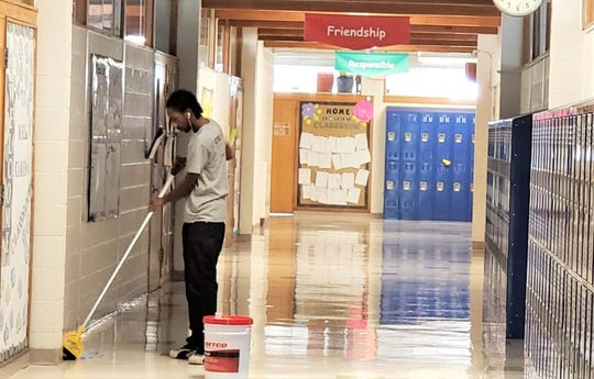 A&C Property Services employee Eric Reid cleans a local school Monday afternoon.