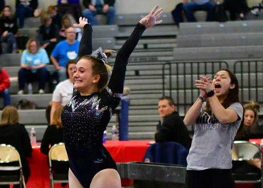 Plymouth gymnastics assistant coach Adrian Hartford cheers on junior captain Ella Seale.