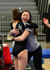 Plymouth gymnastics assistant coach Adrian Hartford celebrates with her player after a routine.