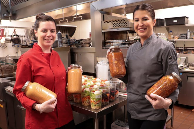 Dringk Eatery + Bar kitchen manager, Katie Kline, left, and owner Carmen Shaw, right, hold family-sized soups they have prepared in Rancho Mirage, Calif. on Monday, March 16, 2020. The restaurant is selling food for stocking one's fridge in the midst of the coronavirus.