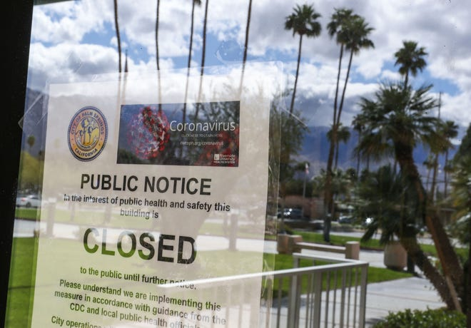 A sign outside of Palm Springs City Hall tells the public it is closed because of the coronavirus, in Palm Springs, March 17, 2020.