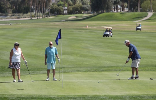 Golfers putt on on the 18th hole of the Legends Course, one of two 18-hole city-owned courses at Tahquitz Creek Golf Resort in Palm Springs,