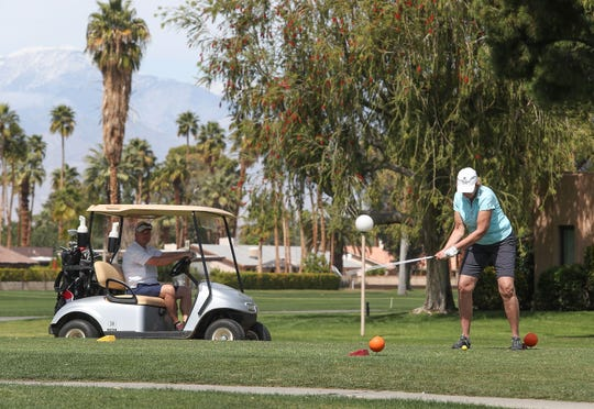 A golfer tees off on the twelfth hole at Tahquitz Creek Golf Resort in Palm Springs, March 16, 2020.  Plenty of golfers were on the course despite the coronavirus Monday.