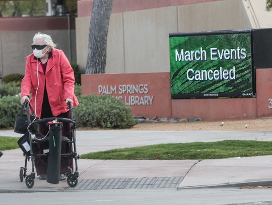 A elderly woman crosses the street near the Palm Springs Public Library, which has been closed because of the coronavirus, in Palm Springs, March 17, 2020.